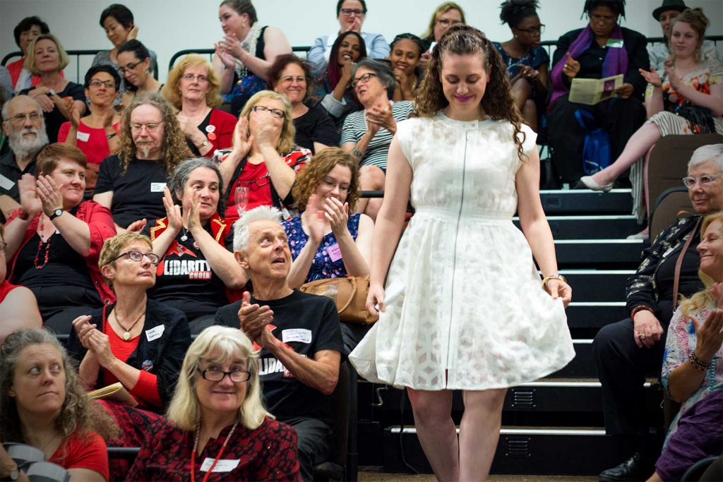 Recipient walking down stairs, through the audience, in a white dress to receive her award