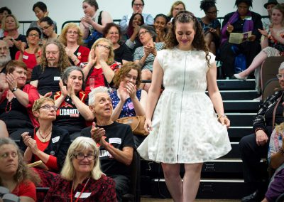 An award recipient in a white dress waking down steps to receive her award
